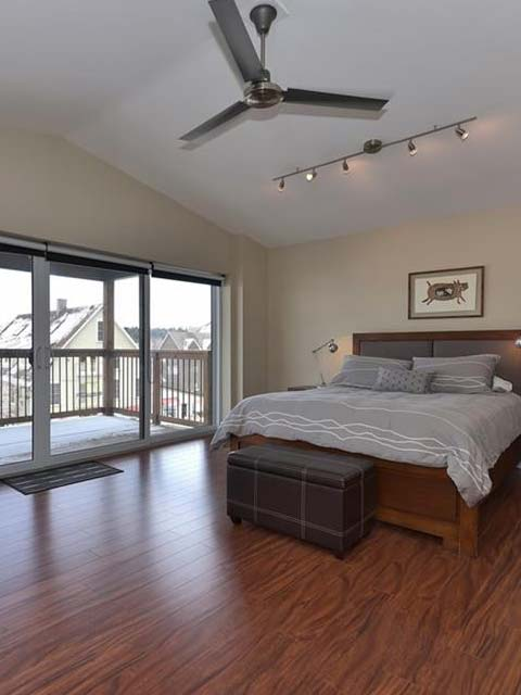 a large bed in the middle of a room with hardwood floors