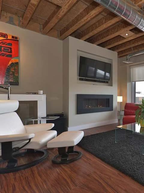 a living room fireplace surrounded by a rug and a white chair