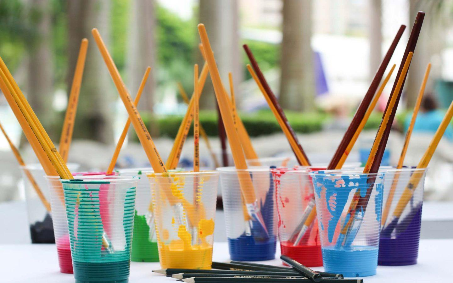 paint brushes sitting in cups filled with different paint colours