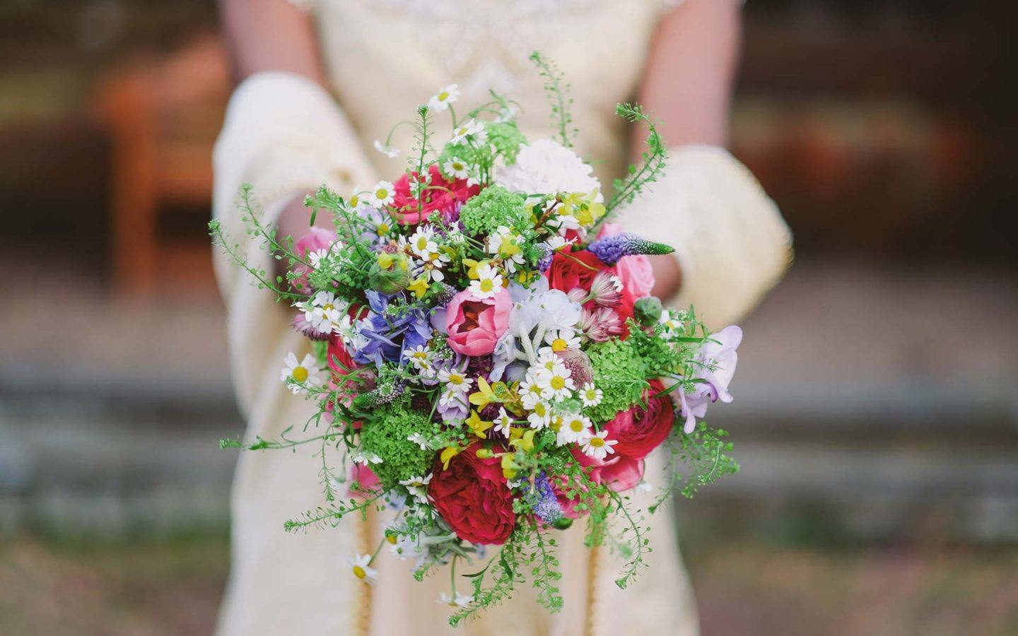 a close up photo of a bridal bouquet held by a bride