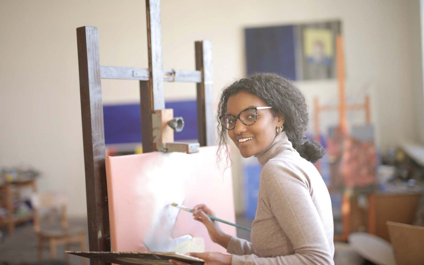 a woman smiling and painting on a canvas