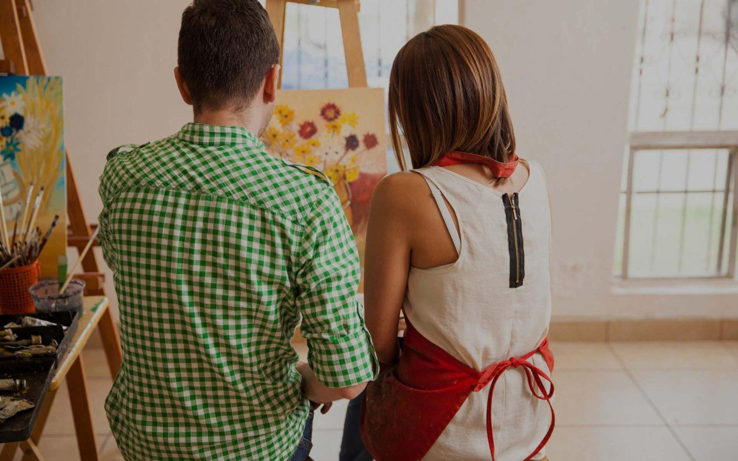 a man wearing a green shirt sits next to.a woman wearing a red apron, both are painting on an easel
