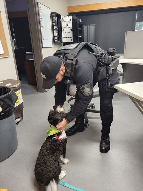 policeman petting a black and white puppy indoors